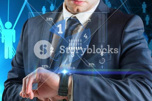 Businessman looking at smart watch with business graph