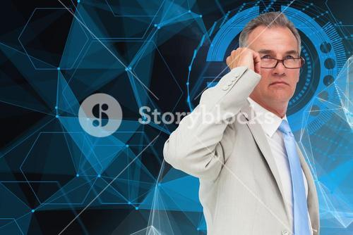 Thoughtful businessman standing in front of business hologram