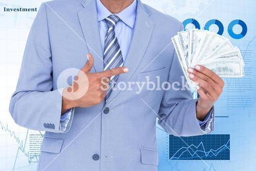 Businessman holding dollars and pointing it