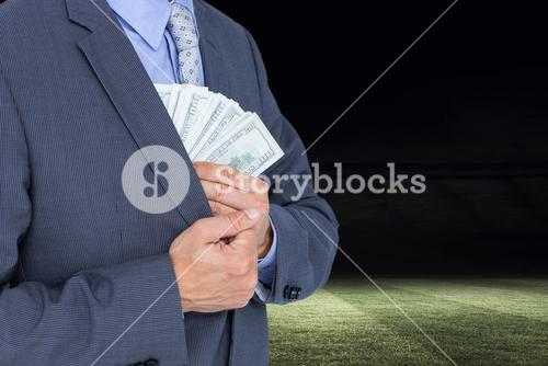 Businessman putting dollars in his pocket