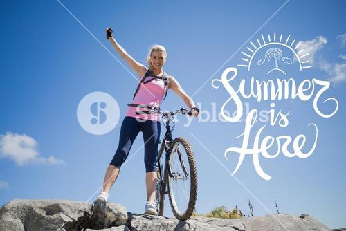 Cyclist standing on a mountain with arm up