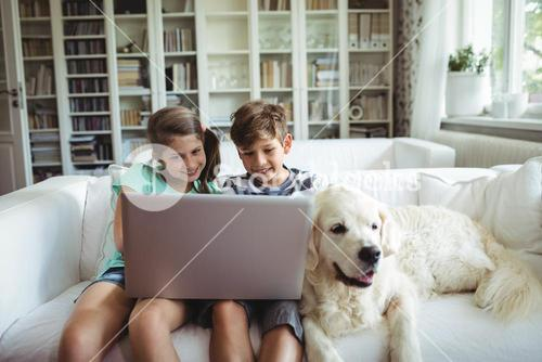 Children using laptop while sitting on a sofa