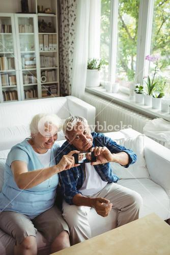 Senior couple taking a photo from mobile phone