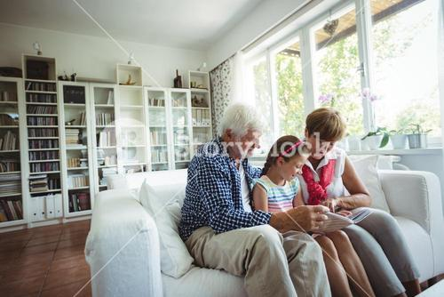 Grandparents and granddaughter looking at photo album in living room