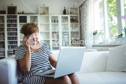 Senior woman talking on mobile phone while using laptop in living room