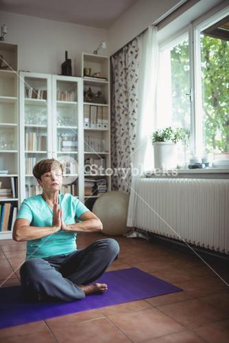 Senior woman meditating in prayer position