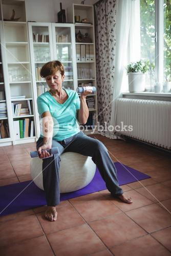 Senior woman exercising with dumbbells on exercise ball