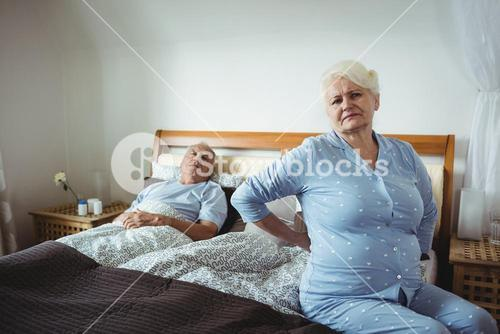 Senior woman suffering from backache sitting on bed