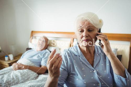Senior woman looking at pill bottle and talking on phone