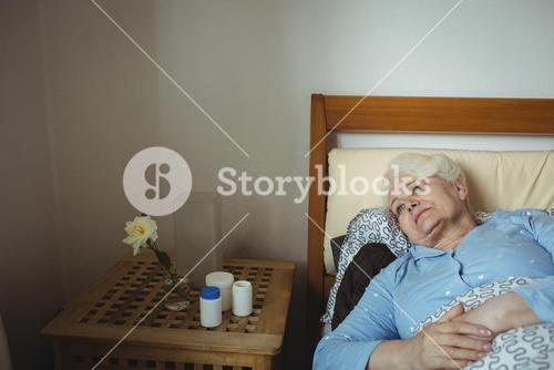 Worried senior woman relaxing on bed