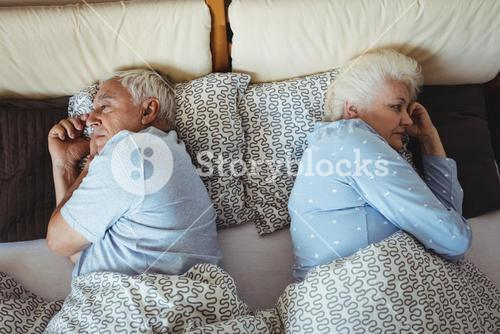 Upset senior couple relaxing on bed