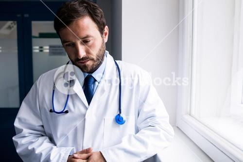 Sad doctor standing in corridor