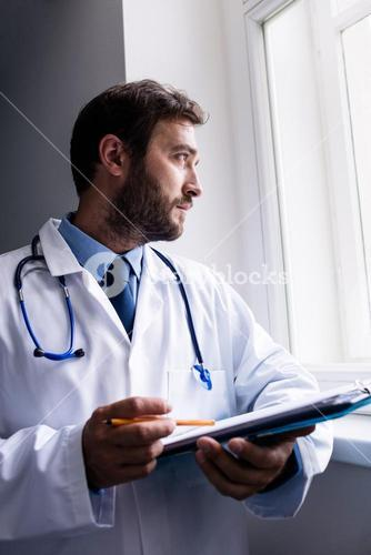 Doctor looking through window while holding clipboard