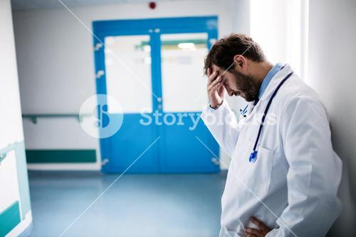 Sad doctor leaning against the wall