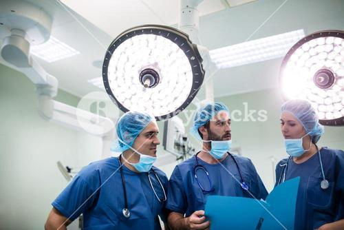 Surgeons discussing patient records in operation room