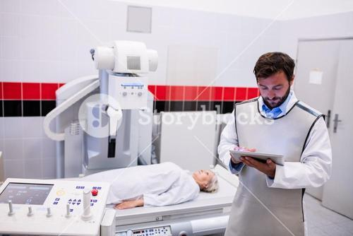 Doctor using digital tablet and patient lying on x ray machine