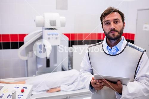Doctor holding digital tablet and patient lying on x ray machine