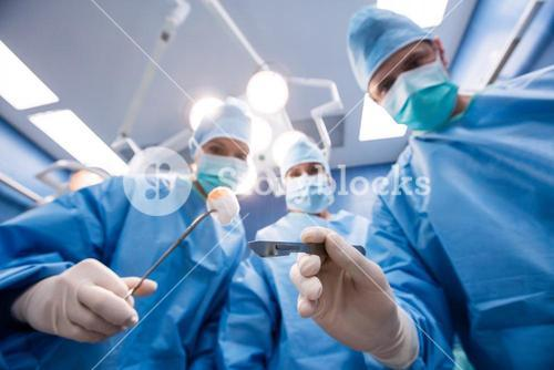 Surgeons holding surgical tools and cotton