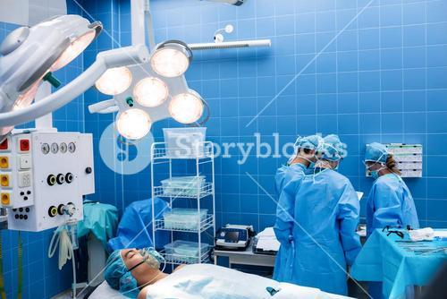 Surgeons interacting with each other while patient lying on operation bed