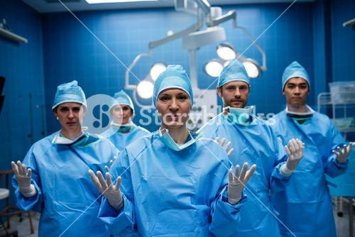 Portrait of surgeons standing with hands raised in operation room