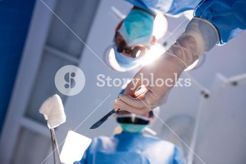 Surgeons holding surgical clamp with cotton swab in operation room