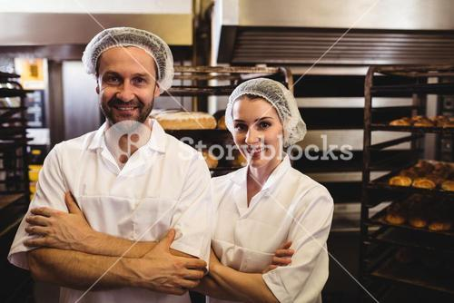 Portrait of female and male baker standing with arms crossed