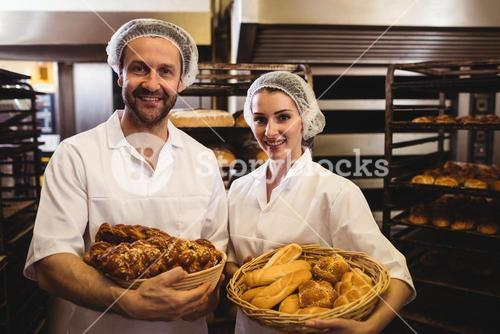 Portrait of female and male baker holding basket of bread and sweet food