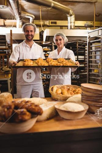 Portrait of female and male baker holding a tray of michetta