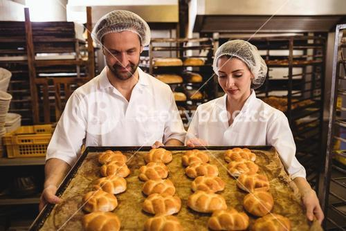 Female and male baker holding a tray of michetta