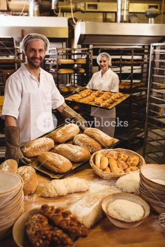 Male and female baker holding tray of loaf and michetta