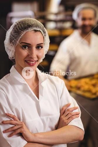 Portrait of female baker standing with arms crossed