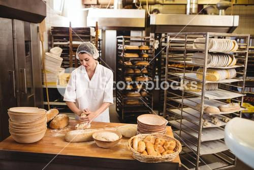 Female baker kneading a dough