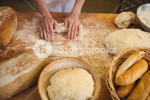 Hands of female baker kneading a dough