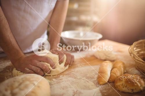 Mid-section of baker kneading a dough