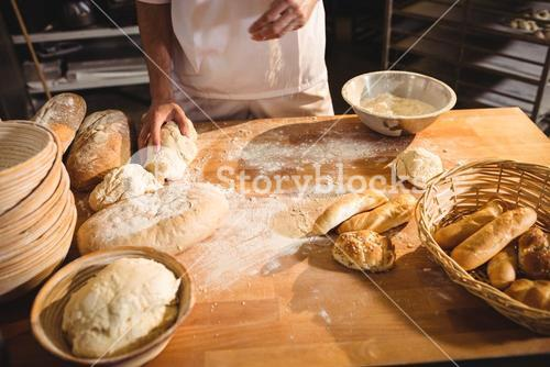 Mid-section of baker ready to knead a dough