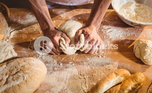 Hands of baker kneading a dough