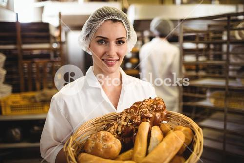 Female baker holding basket of bread and sweet food