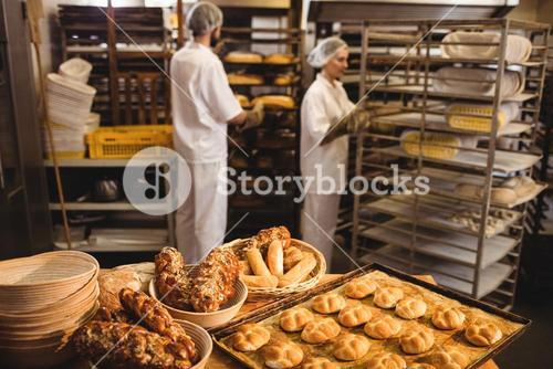 Michetta and sweet food on a table while male and female baker working in background