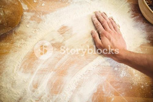 Hand of baker rubbing flour on the table