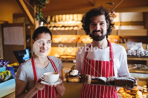 Couple holding a cup of coffee and sweet food