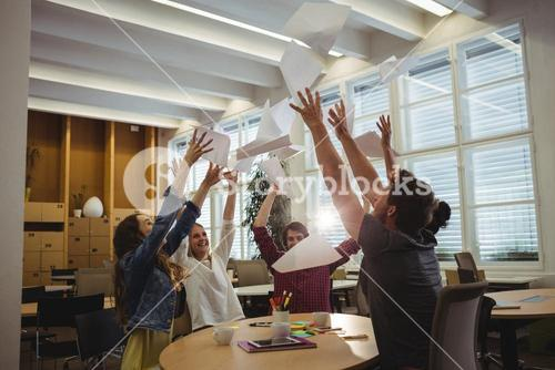 Group of excited business executives throwing paper and having fun