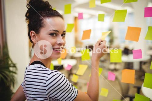 Business executive sticking sticky notes