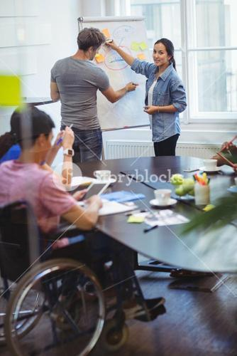 Business executives discussing with their colleagues on whiteboard