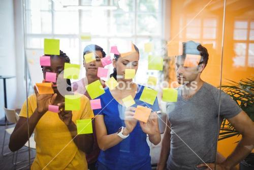 Business executives sticking sticky notes