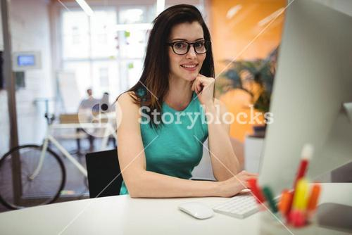Portrait of beautiful female executive sitting at her desk