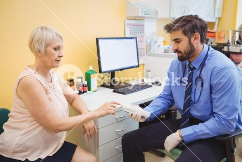 Doctor measuring sugar level of patient with glucometer