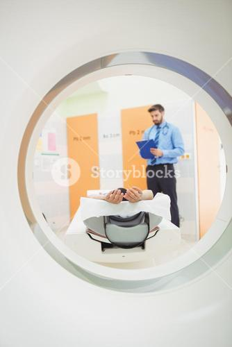 Doctor reviewing chart of patient about to have mri scan