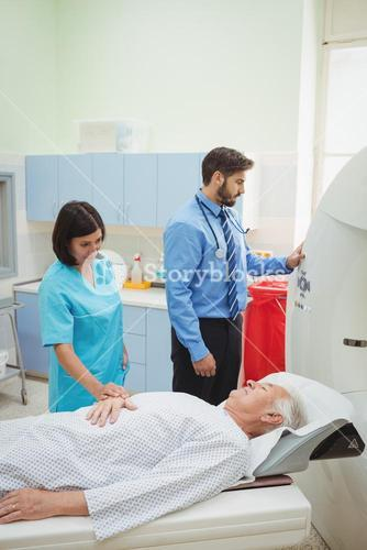A patient is loaded into an mri machine while doctor and technician watching