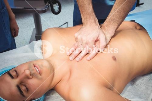 Male surgeon performing cardiopulmonary resuscitation on an unconscious patient