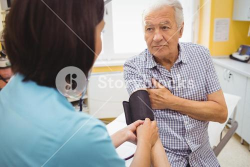 Female doctor checking blood pressure of patient